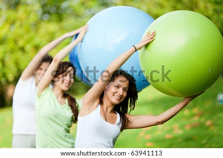 Group of women in a pilates class outdoors - stock photo
