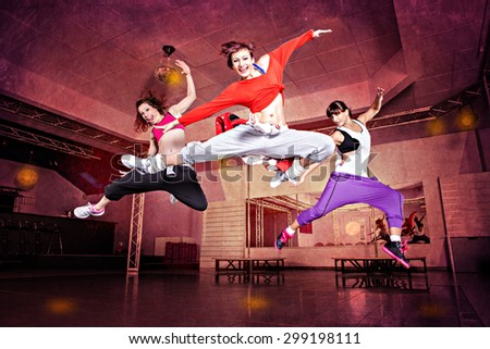 group of  women in sport dress jumping at fitness dance excercise or aerobics