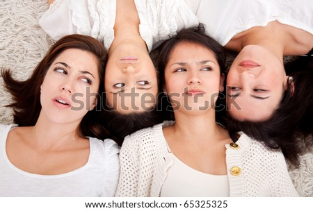 Group of women lying on the floor making faces - stock photo