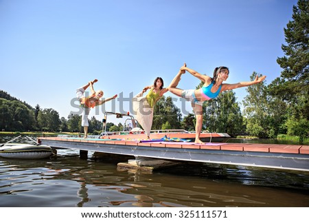 group of women making yoga exercise at a lake - stock photo
