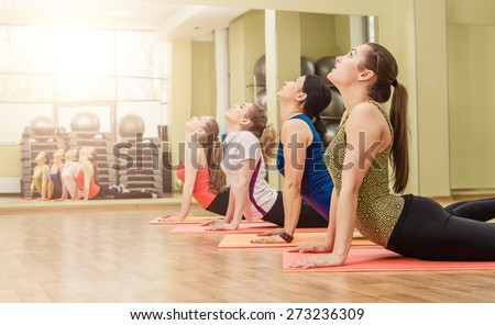 Group of women making yoga stretching in the fitness class, healthy lifestyle concept - stock photo