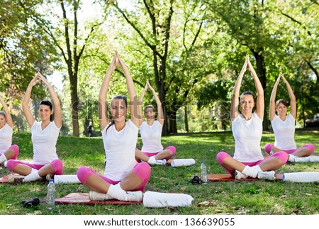 group of   women meditating  in park - stock photo
