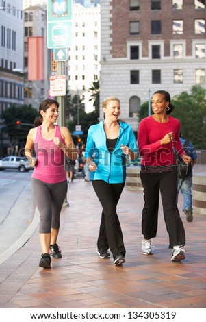 Group Of Women Power Walking On Urban Street - stock photo