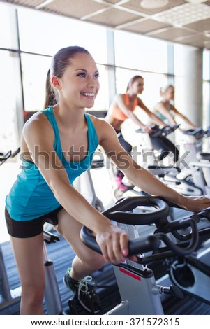 group of women riding on exercise bike in gym
