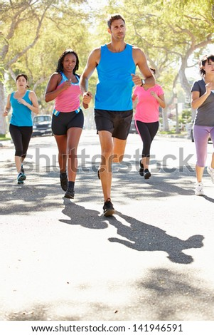 Group Of Women Running Along Street With Personal Trainer - stock photo
