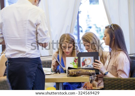 Group Of Women Sitting Around Table Eating Dessert - stock photo