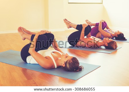 Group of Women Stretching and Relaxing in Yoga Class. Wellness and Healthy Lifestyle. - stock photo