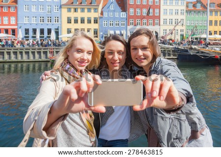 Group of women taking a selfie in Copenhagen with colourful houses on background in Nyhavn district. They are in their twenties and they are wearing smart casual clothes. - stock photo