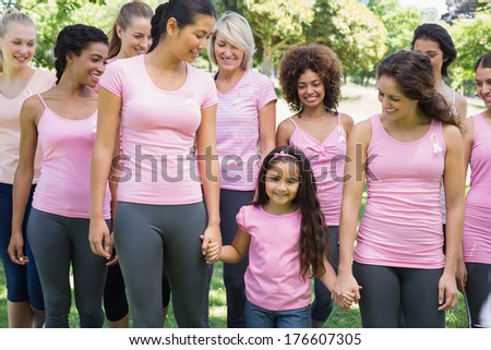 Group of women with girl supporting breast cancer campaign in park - stock photo