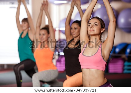 group of women working out in gym, they rising up hands