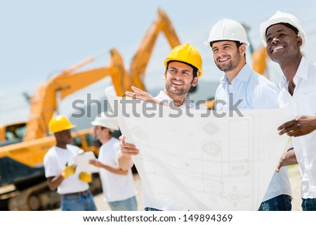 Group of workers at a construction site holding blueprints  - stock photo
