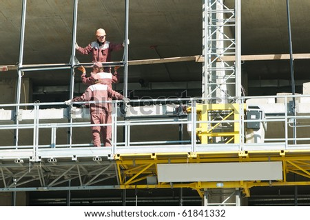 group of workers at restoration building works in mast climbing platform - stock photo