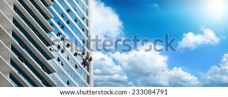 Group of workers cleaning windows on high rise building.Panoramic view - stock photo