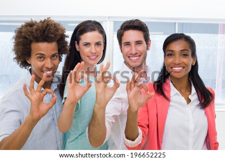 Group of workers giving OK gesture to camera in the office - stock photo