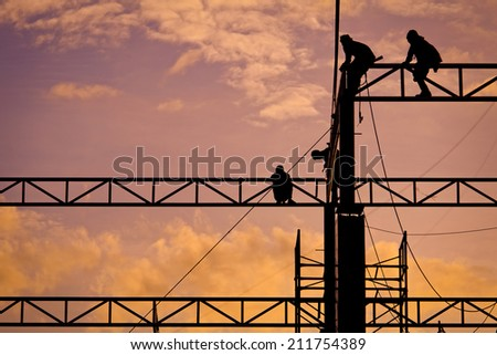 Group of workers working in construction site at sunset - stock photo