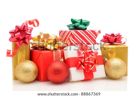 Group of wrapped christmas presents with tree ornaments on a  white background. Horizontal format with reflection. - stock photo