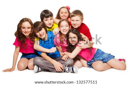 Group of 10 years old kids hugging, smiling, laughing, on white - stock photo