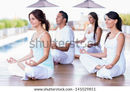 Group of yoga people in a class meditating - stock photo