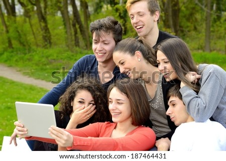 Group of young adults browsing a tablet and having fun outside