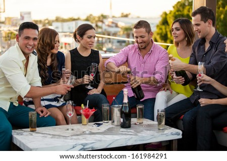 Group of young adults celebrating with champagne and having fun at a bar outdoors - stock photo