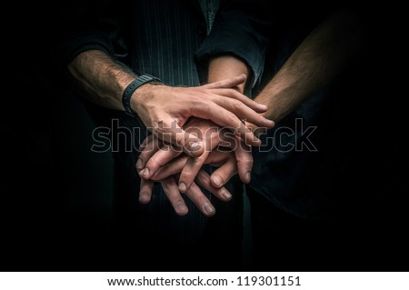 Group of young adults making a pile of hands against dark background - stock photo