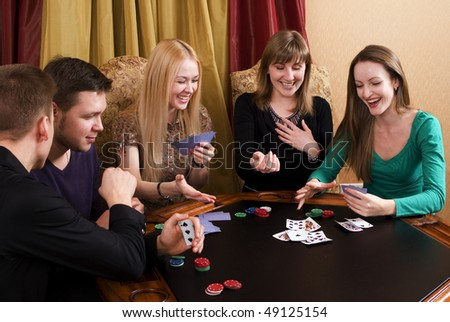 Group of young adults (three girls and two guys) playing cards - stock photo