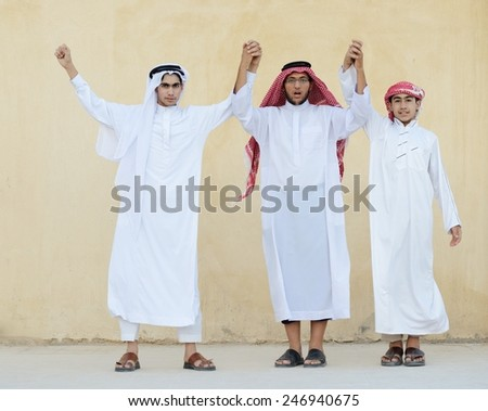 Group of young Arabic Gulf people dancing and celebrating eid party - stock photo