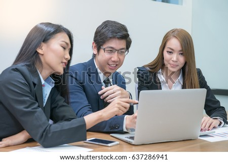 Group of young Asian business man and woman meeting in office happily.
