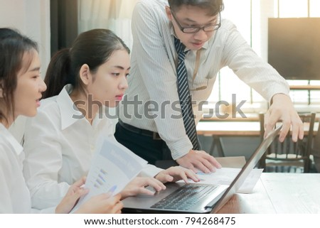 Group of young Asian business people working together on a laptop computer at office. Teamwork brainstroming concept. Selective focus and shallow depth of field.