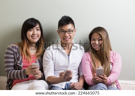 Group of young Asian friends using their smartphones. Happy students using their cell phones.
