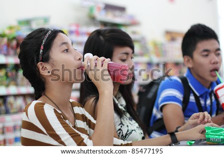 Group of young asian students eating snacks in a restaurant. - stock photo