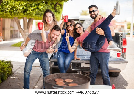 Group of young attractive friends tailgating, drinking beer and having some fun together next to a grill