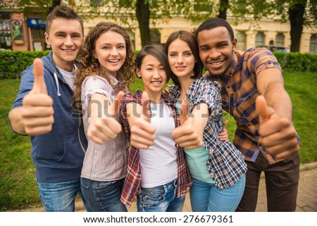 Group of young attractive smiling students dressed casual having fun on campus at the university. - stock photo