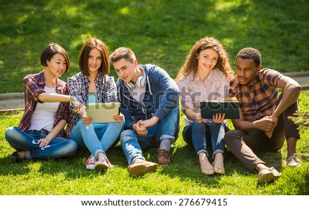 Group of young attractive smiling students dressed casual sitting on the lawn in park and studying.