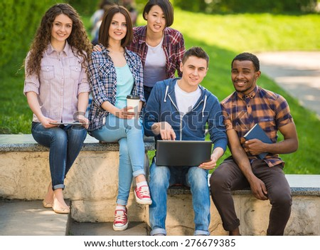 Group of young attractive smiling students dressed casual sitting on the staircase outdoors on campus at the university. - stock photo