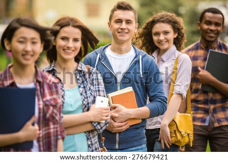 Group of young attractive smiling students dressed casual studying together in park. - stock photo