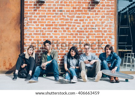 Group of young beautiful multiethnic friends sitting on the floor leaning against brick wall with skate, cell phone and headphones, looking camera, smiling - friendship, happiness, technology concept - stock photo