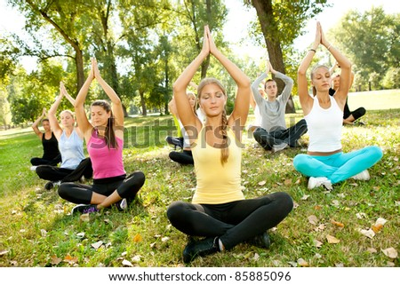 group of young beautiful people doing yoga outdoor - stock photo