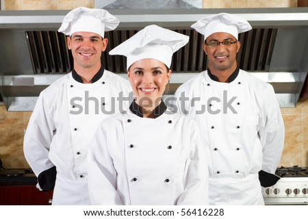 group of young beautiful professional chefs portrait in industrial kitchen - stock photo