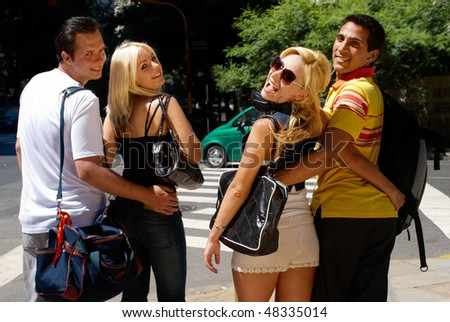 Group of young boys and girls going along street together and having fun - stock photo