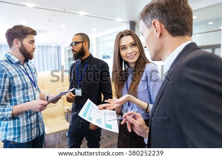Group of young business people discussing financial report and  new project in conference hall - stock photo