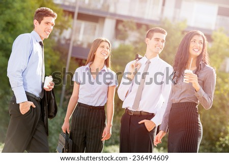 Group of young business people, elegantly dressed, on the coffee break, standing in a park near their company enjoying the sunny day. - stock photo
