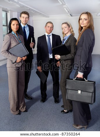 Group of 5 young business people, 3 females and 2 males all confident and looking to camera - stock photo