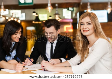 Group of 3 young business people gathered together at a table discussing an interesting idea in the cafe - stock photo