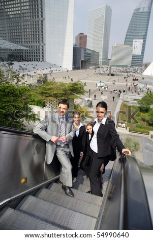Group of young business people on an escalator - stock photo