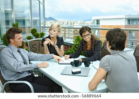 Group of young business people sitting around table on office terrace outdoor, talking and working together. - stock photo