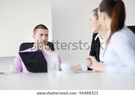Group of young business people sitting in board room during meeting and discussing with paperwork - stock photo