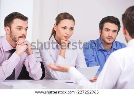 Group of young business people talking on business meeting. over shoulder view of man sitting at meeting in office  - stock photo
