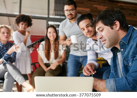 Group of young business people together in a meeting and having a discussion on new creative project. Young designer showing something to team startup meeting. - stock photo