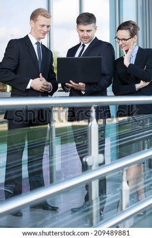 Group of young business people using laptop outdoors, vertical - stock photo
